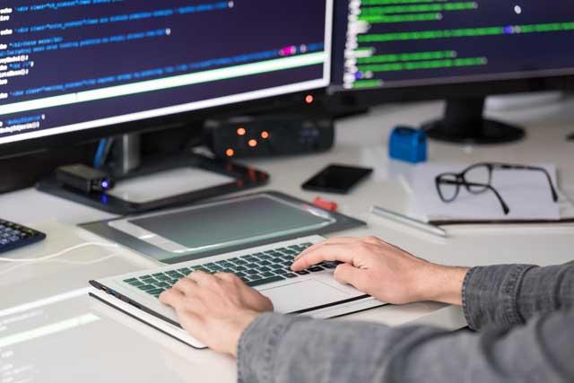 SEの仕事をする人とパソコン