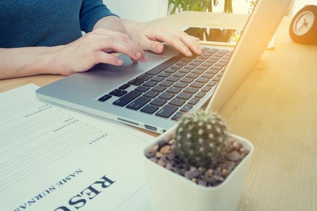 パソコンで転職先企業の情報を調べる人